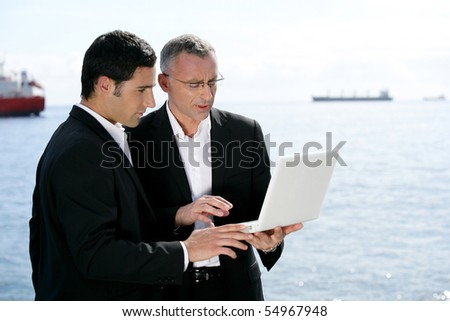 Portrait of two businessmen in front of a laptop computer - stock photo