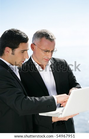 Portrait of two businessmen in front of a laptop computer