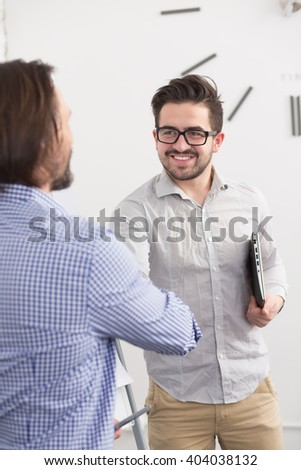 Portrait of two businessmen shaking hands in office. Business partners concluded agreement or contract between their companies. - stock photo