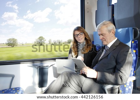 Portrait of two businesspeople traveling on train. Middle age businesswoman using laptop while senior businessman holding digital tablet in his hand and working together.