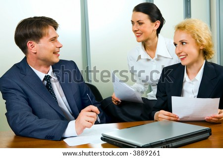 Portrait of two businesswomen and businessman sitting at the table with closed laptop holding documents and discussing questions