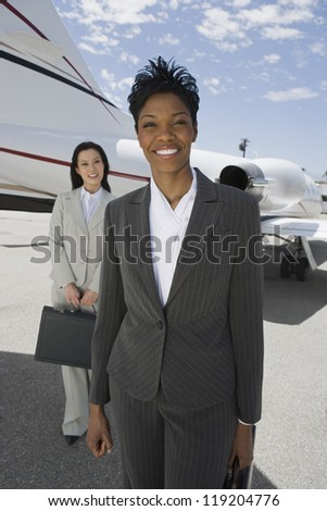 Portrait of two businesswomen in front of private plane - stock photo