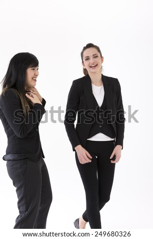Portrait of two Businesswomen laughing. Isolated on white background. Caucasian brunette female model. - stock photo