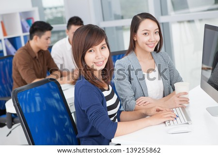 Portrait of two businesswomen working at computer on the foreground