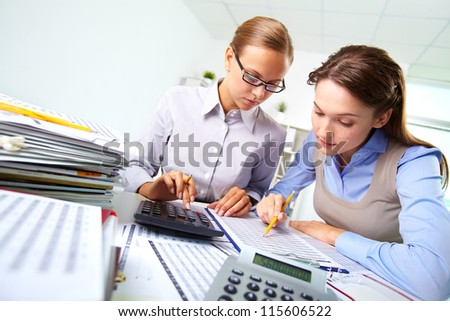Portrait of two businesswomen working with papers and calculator in office - stock photo