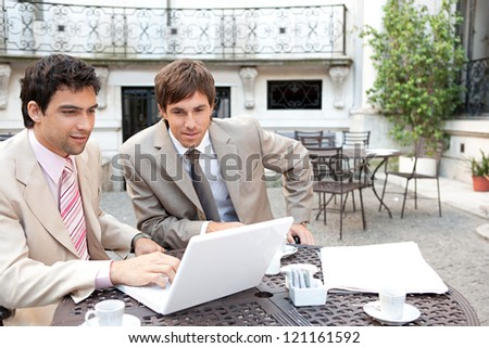 Portrait of two busy businessmen having a meeting in a coffee shop terrace in a classic city financial district with office buildings around them and using a laptop computer.