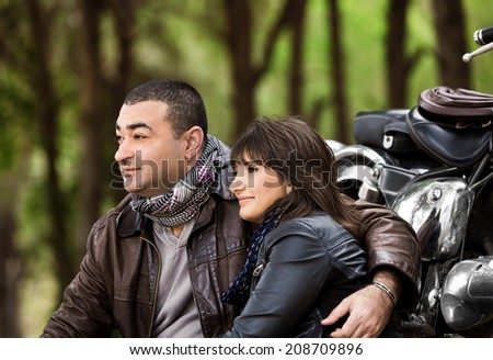 Portrait of two calm people sitting near motorcycle and resting outdoors, romantic relationship, happy adventure, relaxation after extreme trip - stock photo