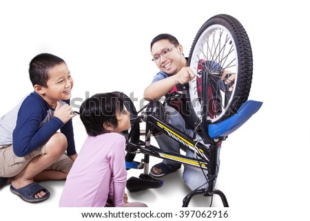 Portrait of two cheerful children and their father fixing a broken bicycle together, isolated on white background - stock photo