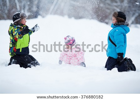 Portrait of Two cheerful happy boys and baby girl playing in winter park, outdoor - stock photo