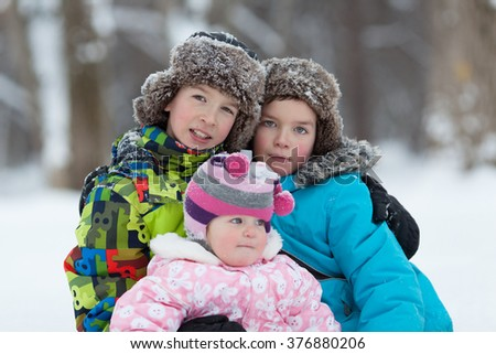 Portrait of Two cheerful happy boys and baby girl playing in winter park, outdoor