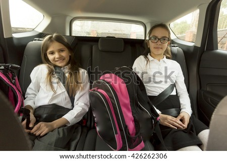 Portrait of two cheerful schoolgirls sitting on car back seat - stock photo