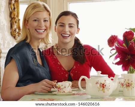 Portrait of two cheerful young women sitting at dining table - stock photo