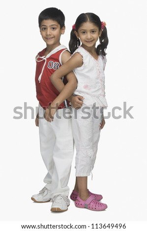 Portrait of two children back to back and hand in hand - stock photo