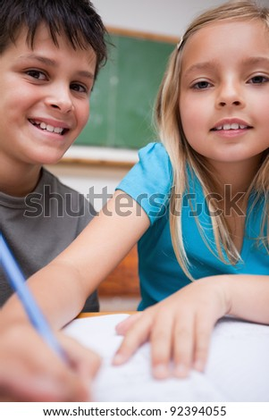Portrait of two children writing in a classroom - stock photo