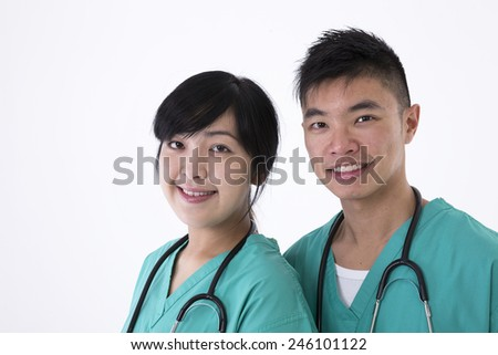 Portrait of two Chinese Medical professionals wearing medical scrubs and stethoscope. Isolated on white background. - stock photo