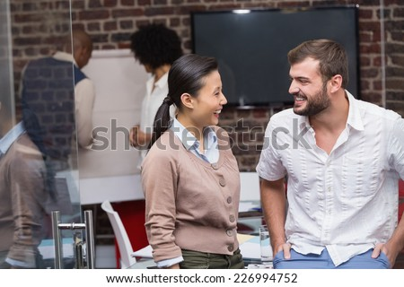 Portrait of two confident young business people standing in office