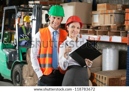 Portrait of two confident young supervisors with book clipboard at warehouse - stock photo