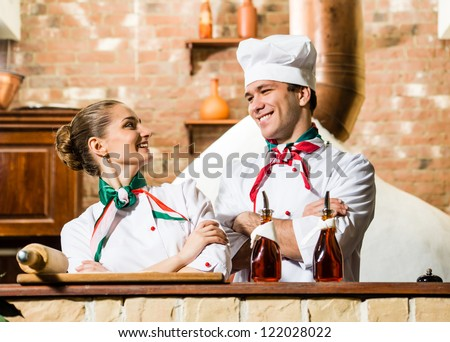 portrait of two cooks, crossing his arms and looking at each other