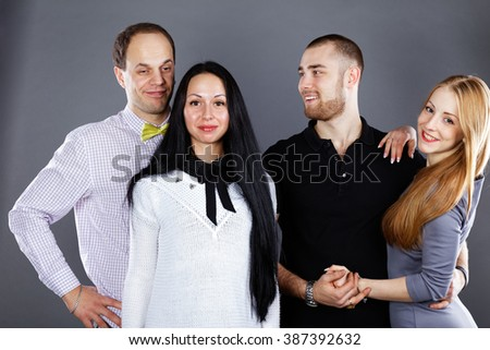 Portrait of two couples on a gray background