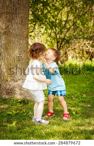 Portrait of two cute adorable baby children toddlers hugging and kissing each other, love friendship in childhood concept, best friends forever  - stock photo