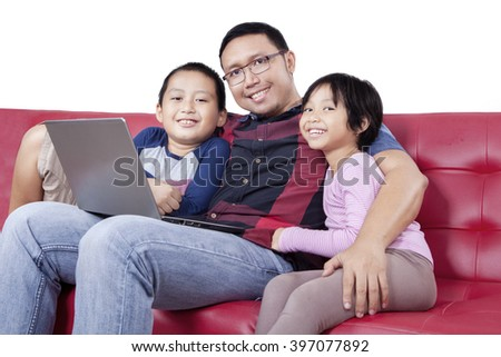Portrait of two cute children and their father sitting on the couch with laptop computer and smiling at the camera