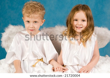 Portrait of two cute children wearing white silk clothing and looking at camera