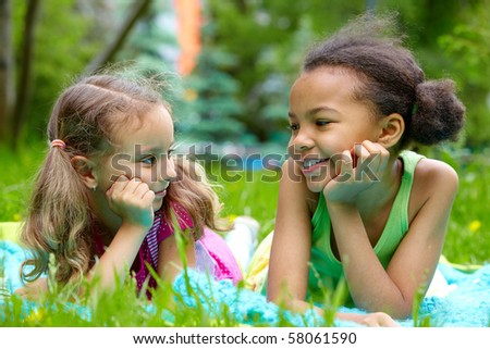 Portrait of two cute girls having rest and looking at one another on summer day - stock photo