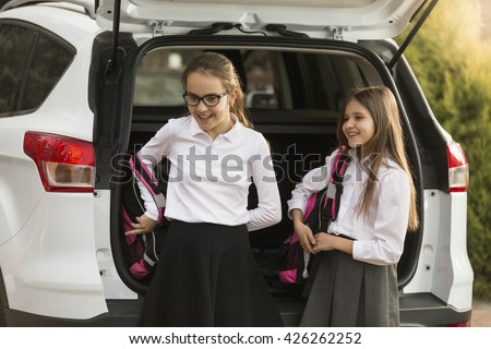 Portrait of two cute girls taking school bags out of car trunk