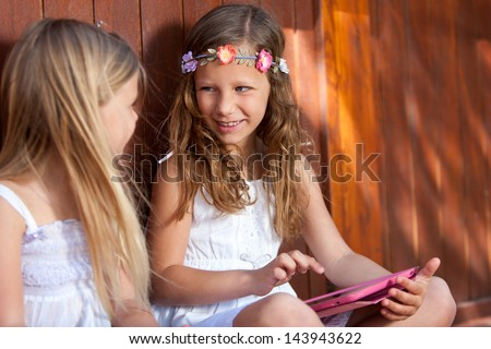 Portrait of two cute kids playing with digital tablet outdoors. - stock photo