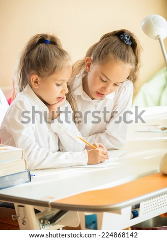 Portrait of two cute schoolgirls writing at textbook at desk - stock photo