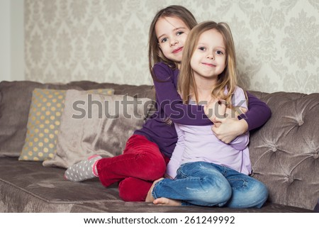 Portrait of two cute sisters at home. Family. Indoor lifestyle portrait of couple beautiful sisters best friends. Cozy home atmosphere