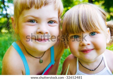 Portrait of two cute smiling sisters or friends - stock photo