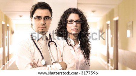 Portrait of two determined young doctors, taken on the hospital corridor. - stock photo