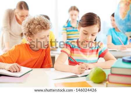 Portrait of two diligent pupils drawing at lesson - stock photo