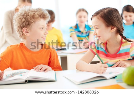 Portrait of two diligent pupils interacting while drawing at lesson - stock photo