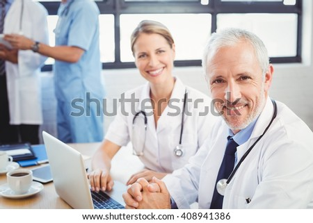 Portrait of two doctors smiling in conference room in hospital - stock photo