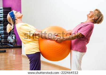 Portrait of two Elderly women stretching muscles together with fitness ball in gym.