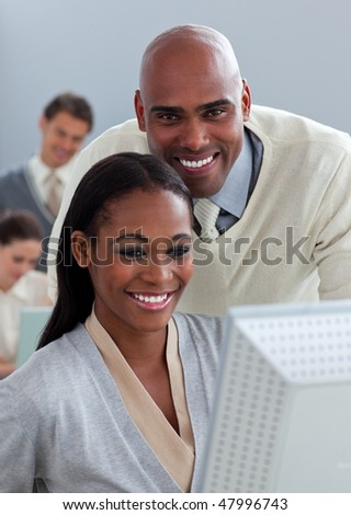 Portrait of two enthusiastic businesspeople working at a computer in the office