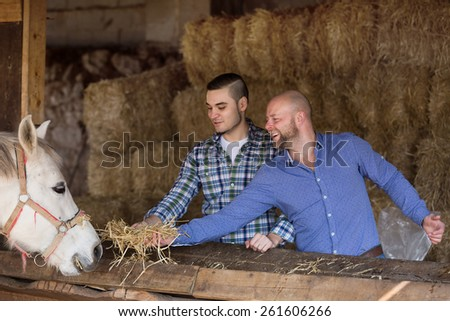Portrait of two farmers with the pitchforks in settlement  - stock photo