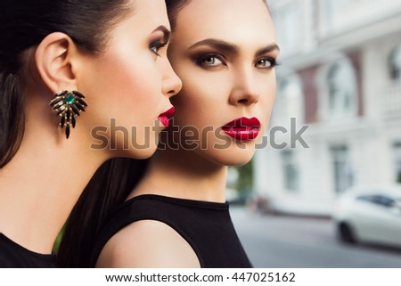 Portrait of two fashion models. Young beautiful stylish brunette sisters with bright makeup and red lipstick, close up. Outdoor. - stock photo