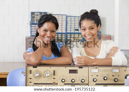 Portrait of two female engineering students smiling at lab bench in electrical engineering laboratory - stock photo