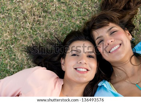 Portrait of two female friends looking happy lying outdoors