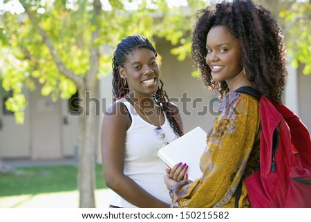 Portrait of two female students on college campus - stock photo