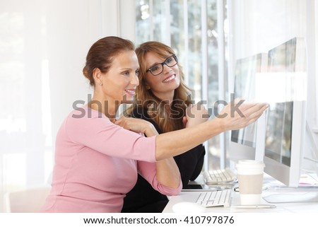 Portrait of two financial businesswomen discussing about new strategy while working together on computer.  - stock photo