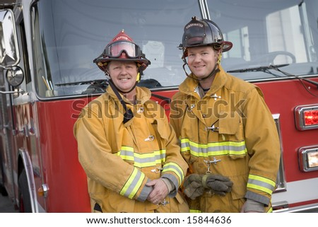 Portrait of two firefighters by a fire engine - stock photo