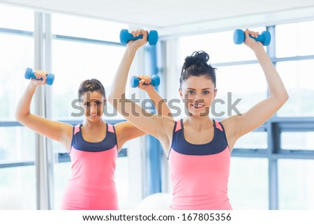 Portrait of two fit women lifting dumbbell weights in a bright gym - stock photo