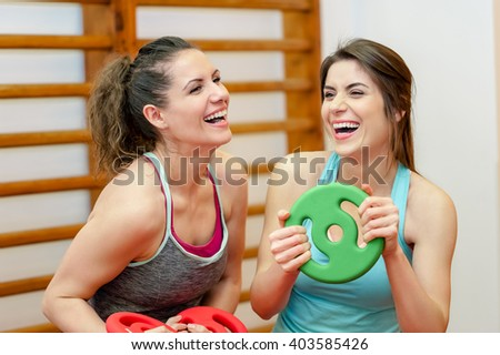 Portrait of two fit young women smiling in a exercise room holding weights - sport, fitness, lifestyle and people concept. - stock photo