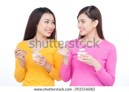 Portrait of two friendly asian woman friends eating yoghurt promoting healthy lifestyle and dieting - stock photo