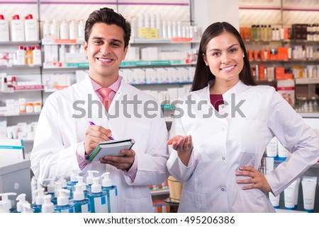 Portrait of two friendly smiling pharmacists working in modern pharmacy