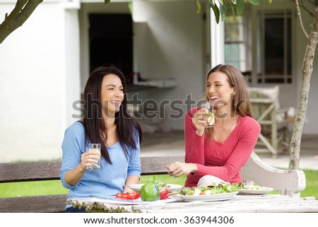 Portrait of two friends talking and having lunch together